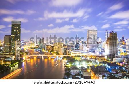 Aerial view of Bangkok Skyline along Chao Phraya River at dusk. Beautiful blue sky and night light of Bangkok city, Thailand background. Bangkok transportation with Taksin bridge across river. - stock photo