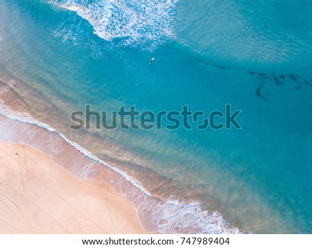 Aerial view of beach coastline with single surfer.