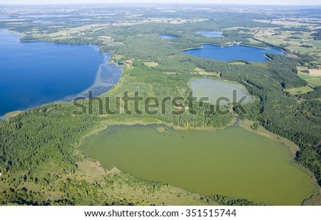 Aerial view of beautiful autumnal landscape of Mazury, Poland - very shallow Skarz Lake in the foreground, farther on the left Dargin Lake, on the right Dgal and Warniak Lakes
