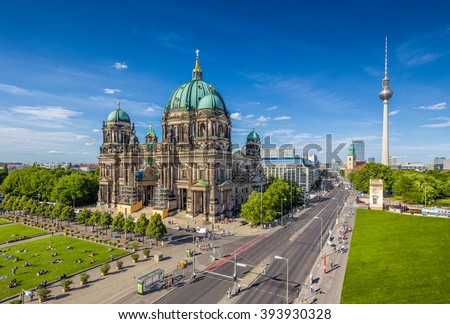 Aerial view of Berlin Cathedral at Lustgarten park with famous TV tower in the background on a sunny day with blue sky and clouds in summer, Berlin Mitte district, Germany - stock photo