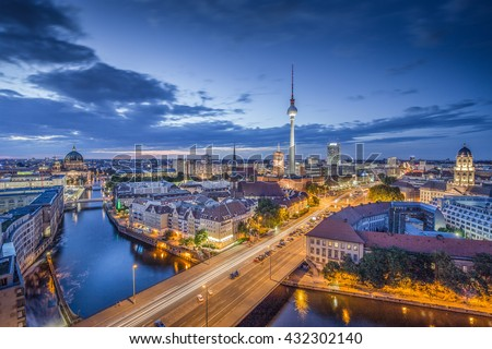 Aerial view of Berlin skyline with famous TV tower and Spree river in twilight during blue hour at dusk with dramatic clouds, Germany - stock photo