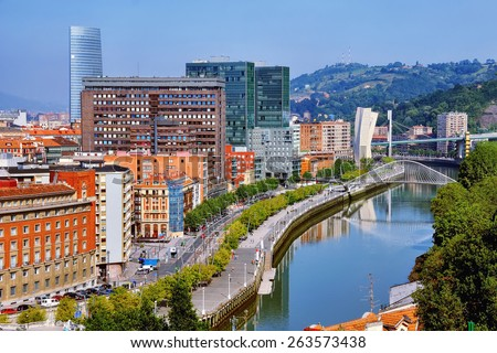 Aerial view of Bilbao, Spain city downtown with a Nevion River, Zubizuri Bridge and promenade. Mountain at the background, clear blue sky. - stock photo