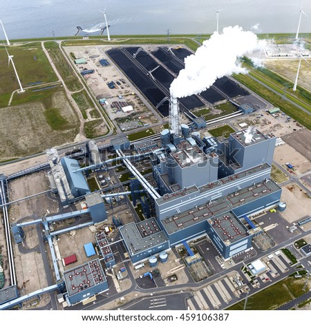 Aerial view of blue colored power plant with smoke coming out of the chimney. It is located in the Eemshaven near Delfzijl, in the province of Groningen.
