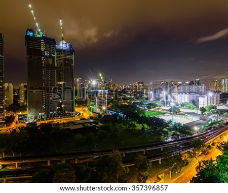 Aerial view of building construction site near the railroad track at Redhill neighborhood in Singapore at night. Urban high rise construction concept