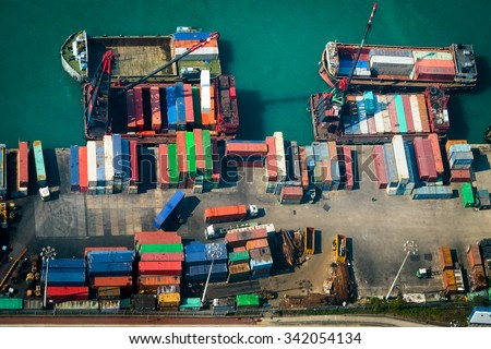 Aerial view of cargo ships loaded by crane with cargo containers at a busy port terminal. Hong Kong - stock photo