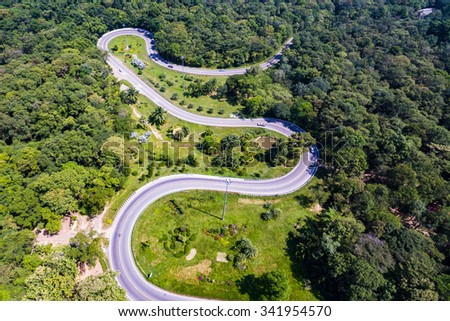 Aerial view of cars are going through a curve  road on the mountain - stock photo
