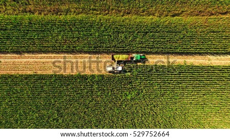 aerial view of Claass harvester picking on field with John Deere tractor in italian countryside Italy-Pavia 14 September 2016