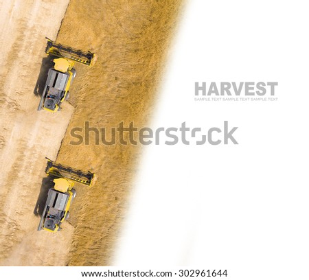 Aerial view of combine harvester on wheat field. Industrial background on agricultural theme. Picture with space for your text. - stock photo