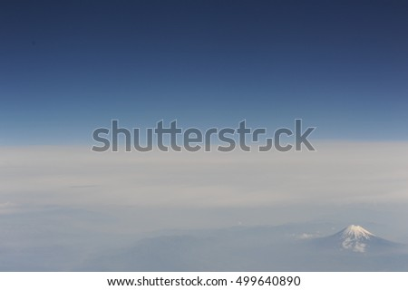 Aerial view of cone-shaped snow-covered Mount Fuji with a blue sky and mist