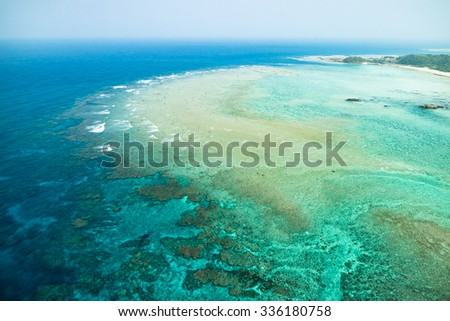 Aerial view of coral reef and clear blue tropical sea from paragliding flight, Amami Oshima Island, Kagoshima, Japan