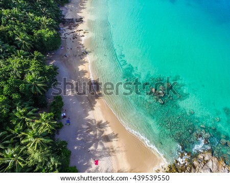 Aerial view of cozy white sand beach with turquoise clear sea water, and some people on the beach. Banana Beach, Phuket, Thailand. - stock photo