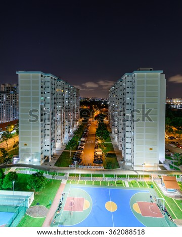 Aerial view of Eunos neighborhood in Singapore at blue hour. The new estate HDB housing complex with outdoor tennis and basketball court, faculties car park, and green garden at the center. - stock photo