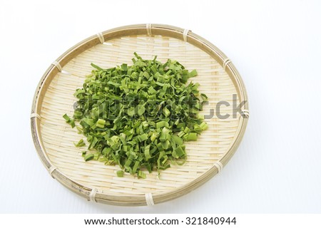 Aerial view of finely shredded or chopped pandan leaf in a round bamboo plate. The leaves after drying is used for making tea due to its nice sweet fragrance and medicinal benefit to combat body heat. - stock photo
