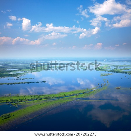 Aerial view of flood-land beside great river during summer.
