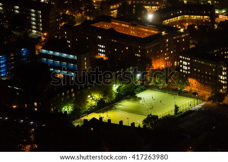 Aerial view of football pitch at night with amateur football players playing the game in the city - stock photo