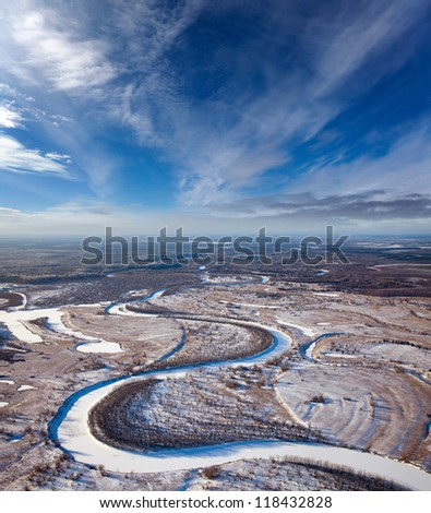 Aerial view of forest of plain and small river during a winter day. - stock photo