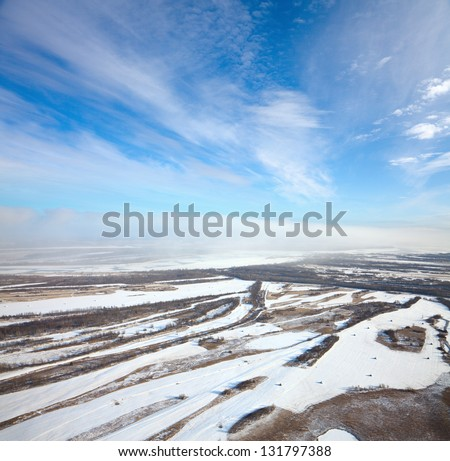 Aerial view of forest of plain and small river during a winter day. Snow lies on the field with haystacks. - stock photo
