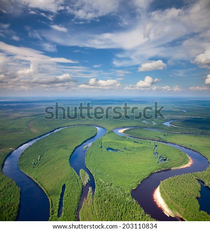 Aerial view of forest river during calm summer day. - stock photo