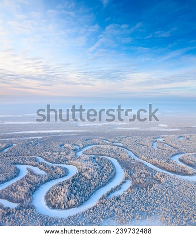 Aerial view of forest river during cold winter day. Magnificent hoarfrost is on trees.  A winter forest is in a hard frost. - stock photo