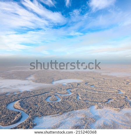 Aerial view of forest river during frozen winter day. Magnificent hoarfrost on trees.  A winter forest on rising in a hard frost. - stock photo