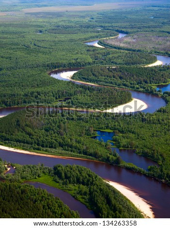 Aerial view of forest river which is on woodland in the cloudy summer day during a flight.