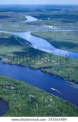 Aerial view of forest the river during summer day. The ship with barge moves along the river. - stock photo