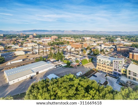 aerial view of Fort Collins downtown with Front Range of Rocky Mountains on horizon, late summer - stock photo