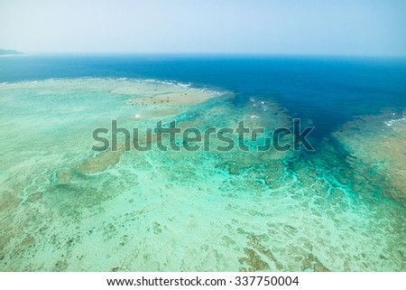 Aerial view of fringing coral reef and clear turquoise tropical sea, Amami Oshima Island, Kagoshima, Japan - stock photo
