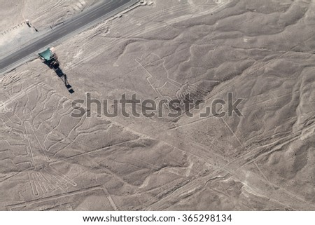 Aerial view of geoglyphs near Nazca - famous Nazca Lines, Peru. In the center, Hands figure is present, on the left side, part of Tree figure. Observation tower and Panamericana highway on left side. - stock photo