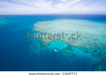 Aerial view of Great Barrier Reef and yacht from helicopter, Queensland, Australia
