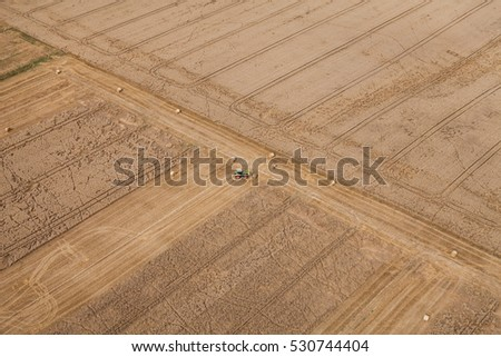 aerial view of harvest fields with tractor in Poland in summer