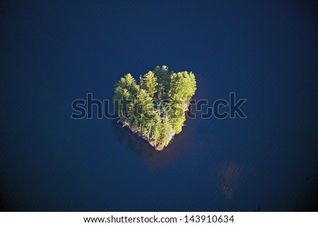 Aerial view of heart shaped island with a house in Maine - stock photo