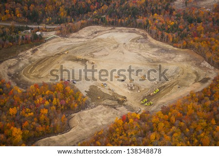 Aerial view of heavy equipment excavating site surrounded by fall foliage, Stowe, Vermont, USA - stock photo