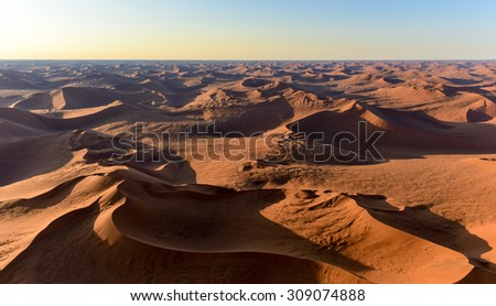 Aerial view of high red dunes, located in the Namib Desert, in the Namib-Naukluft National Park of Namibia. - stock photo