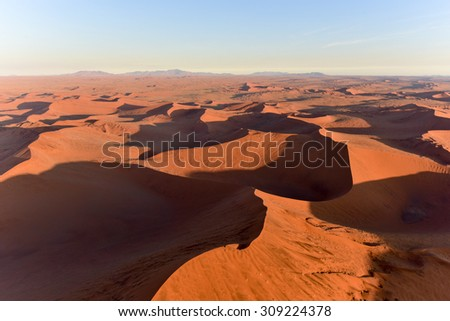 Aerial view of high red dunes, located in the Namib Desert, in the Namib-Naukluft National Park of Namibia.