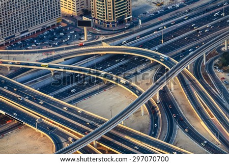 Aerial view of highway road intersections with traffic in a big city (Dubai) at sunset. Transportation concept.  - stock photo