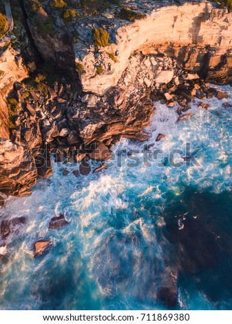 Aerial view of incoming waves into a rock cliff.