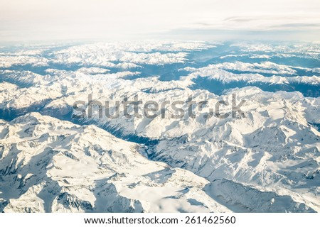 Aerial view of italian Alps with snow and misty horizon - Travel concept and winter vacation  on white snowy mountains - Trip wander to exclusive luxury destinations - stock photo