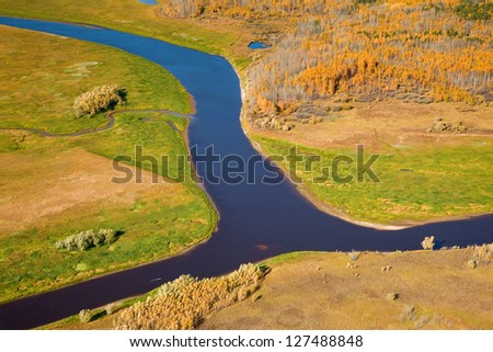 Aerial view of lowland of forest river a autumn during a flight. - stock photo
