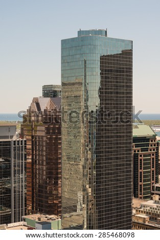 Aerial view of main highrise buildings or modern architecture of Toronto downtown. Beautiful skyscraper with reflection of houses in a glass over blue sky. - stock photo