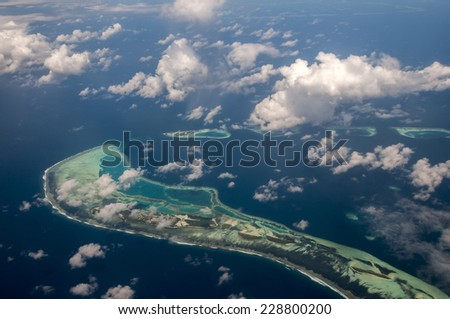 Aerial view of Maldives atoll and reefs seen from a sea plane - stock photo