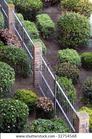 Aerial view of manicured bushes and brick and wrought iron fence - stock photo
