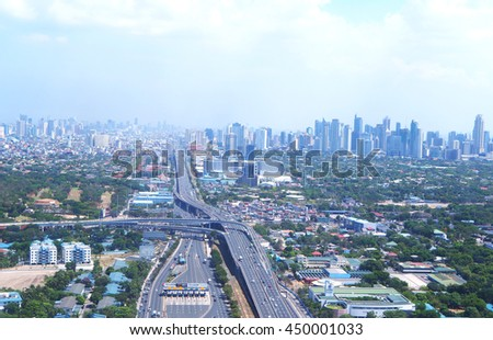 Aerial view of Manila, Philippines with clouds and smog in the background.