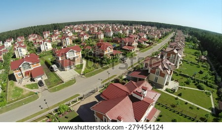 Aerial view of many similar houses in cottage settlement at sunny summer day. - stock photo