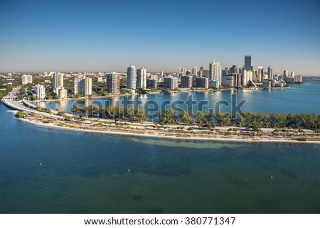 aerial view of miami's brickell avenue skyline and rickenbacker causeway on clear, sunny morning