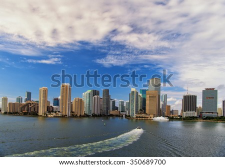 Aerial view of  Miami skyscrapers with blue cloudy sky,  boat sailing next to  Miami downtown - stock photo