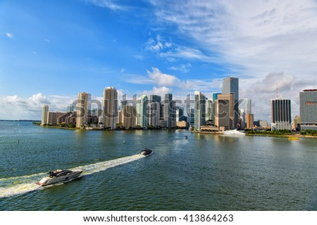 Aerial view of Miami skyscrapers with blue cloudy sky, boat sailing next to Miami downtown