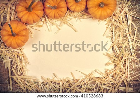 Aerial View of Mini Pumpkins on hay covered Rustic Wood Board Background with cream paper with room or space for copy, text, your words.  Horizontal with trendy vintage, warm sepia cross processing.
