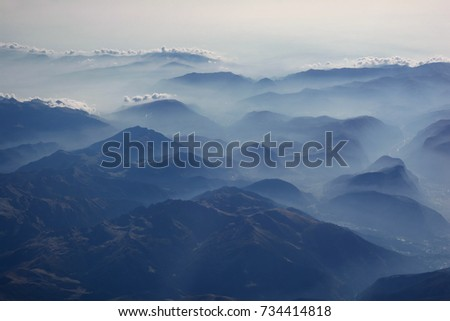 Aerial view of misty mountains and clouds above the mountain peaks, blue tinted