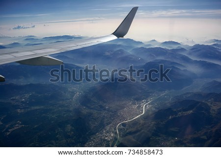 Aerial view of misty mountains, city, river, clouds and a plane wing, opposite the sunlight